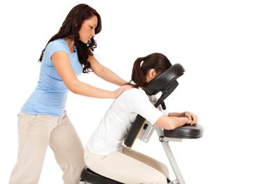 Massage therapist giving woman chair massage.