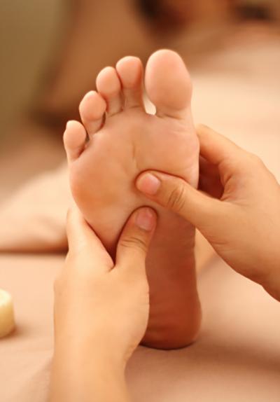 Person's foot receiving neck and foot reflexology massage.