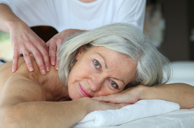Older woman receiving geriatric massage therapy.