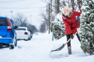 Woman Shoveling her Parking Lot after a Snowstorm